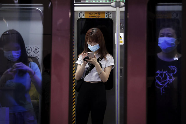 Commuters wearing face masks to protect against the new coronavirus ride in a subway train in Beijing, Wednesday, July 29, 2020. China reported more than 100 new cases of COVID-19 on Wednesday as the country continues to battle an outbreak in Xinjiang. (Photo by Andy Wong/AP Photo)