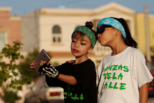 "Children residents take a selfie as they wait for the police to dance, an unconventional approach to connect the police with the community in rough neighbourhoods, as part of the ""Tirando Barrio"" (Marking territory) programme in Saltillo, Northern Mexico September 9, 2016. T-Shirt reads ""Street Dancers"". (Photo by Daniel Becerril/Reuters)"