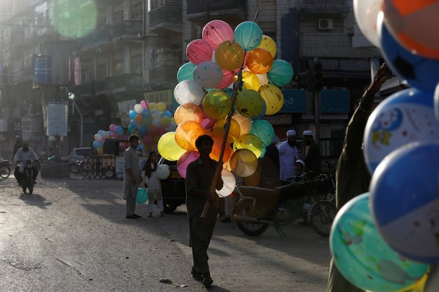 A boy walks with a bunch of balloons to attract children while selling outside a mosque during Eid al-Adha celebrations in Karachi, Pakistan on August 1, 2020. (Photo by Akhtar Soomro/Reuters)