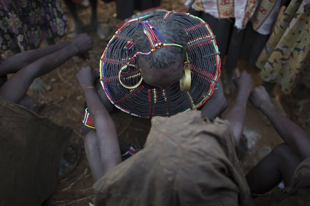 A Pokot woman performs a circumcision on a girl in a village about 80 kilometres from the town of Marigat in Baringo County, October 16, 2014. (Photo by Siegfried Modola/Reuters)