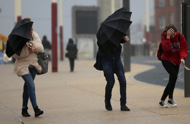 Students brave high winds and rain on Blackpool promenade as Britain prepares for high winds over the next two days on October 20, 2014 in Blackpool, England. (Photo by Christopher Furlong/Getty Images)