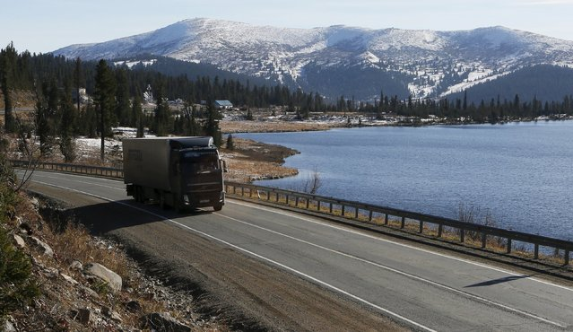 """A truck drives along the M54 """"Yenisei"""" highway in the Western Sayan mountains along the bank of the Oyskoye Lake near an administrative border with Tuva region south of Krasnoyarsk, Southern Siberia, Russia, October 11, 2015. (Photo by Ilya Naymushin/Reuters)"""
