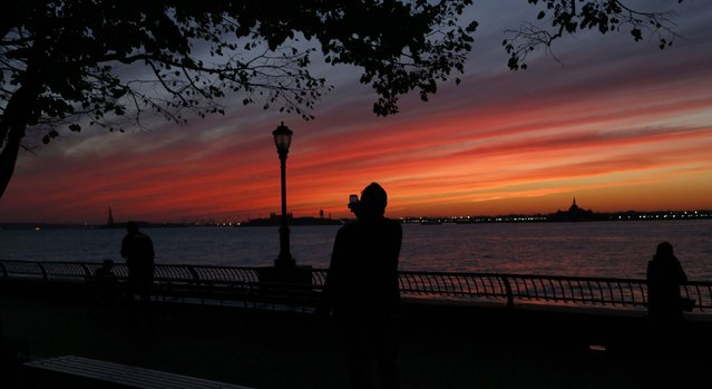 A man uses a smart phone as he take a picture in Battery Park at sunset alongside the Hudson River on an autumn day in New York November 9, 2014. (Photo by John Schults/Reuters)