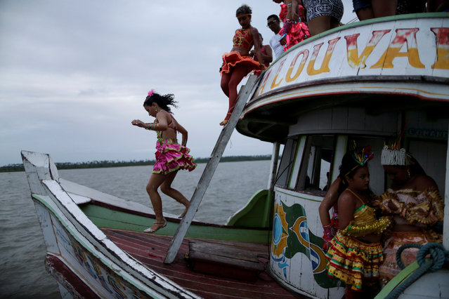 "A member of the ""Bloco Real Folia"" group is seen descending stairs during Carnival of the Waters, where costumed and colorful boats navigate the river Jaituba, around the islands near the city of Cameta, Brazil on February 8, 2018. (Photo by Ueslei Marcelino/Reuters)"