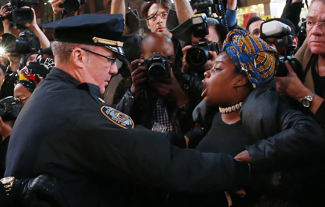 NYPD officers attempt to detain a demonstrator protesting against the verdict announced in the shooting death of Michael Brown, in Times Square, New York, November 25, 2014. (Photo by Mike Segar/Reuters)