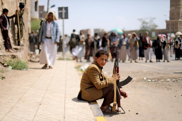 A boy holds a rifle as he sits at the site of a rally held by followers of the Shi'ite Houthi movement to commemorate the Ashura, the holiest day on the Shi'ite Muslim calendar, in Sanaa, Yemen on August 30, 2020. (Photo by Khaled Abdullah/Reuters)