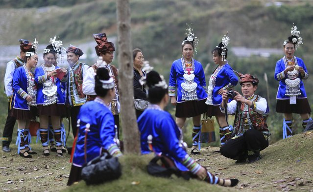 An ethnic minority Dong man (2nd R), dressed in a traditional costume, takes pictures of his fellow choir members during a Kam Grand Choir competition in Congjiang county, Guizhou province November 28, 2014. About 100 choirs made up of Dong residents in Guizhou, Guangxi and Hunan provinces gathered in Congjiang on Friday for a two-day singing competition, local media reported. (Photo by Sheng Li/Reuters)