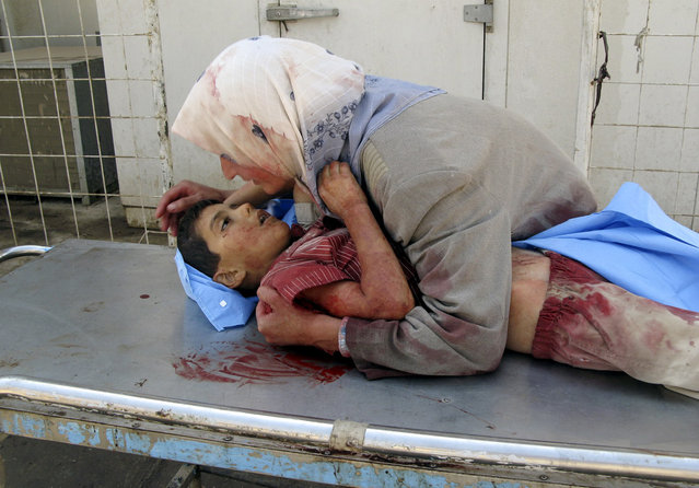 A woman takes her dead son into her arms, as she grieves for her six-year-old son, Dhiya Thamer, who was killed when their family car came under fire by unknown gunmen in Baqouba, 60 kilometers (35 miles) northeast of Baghdad, on September 16, 2007. The boy's ten-year old brother, Qusay, was injured in the attack as the family returned from enrolling the children in school, where Dhiya was to begin his first year. (Photo by Adem Hadei/AP Photo/The Atlantic)