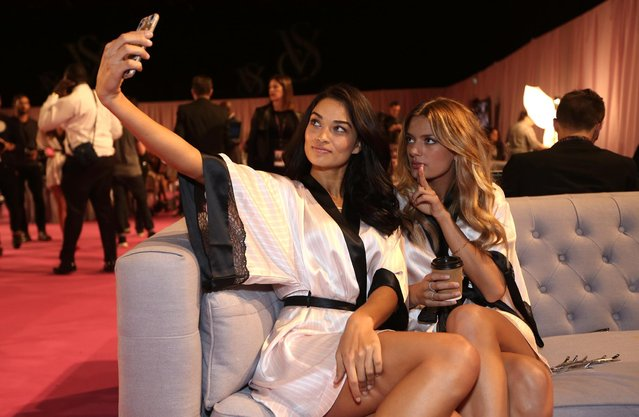 Models Shanina Shaik and Kate Grigorieva pose for a selfie backstage at the Victoria's Secret fashion show in London, Tuesday, December 2, 2014. (Photo by Joel Ryan/Invision/AP Photo)