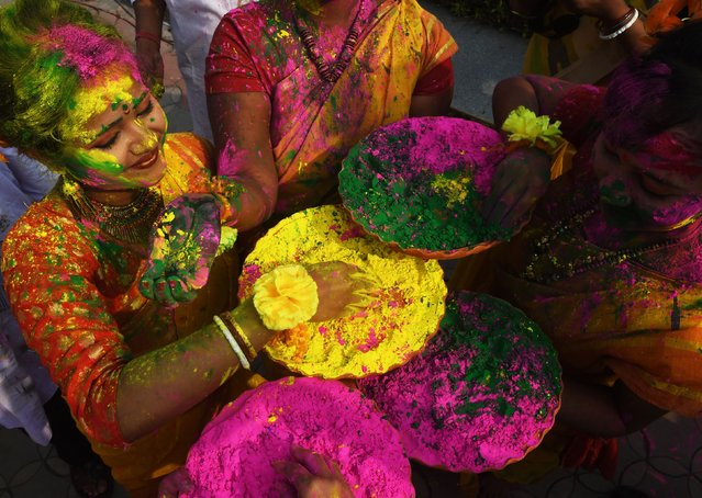 Indian students play with coloured powders to celebrate Holi festival in Kolkata on March 1, 2018. (Photo by Dibyangshu Sarkar/AFP Photo)