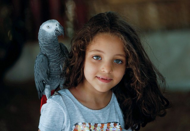A parrot stands on a girl's shoulder on the first day of reopening the Giza zoo, amid the outbreak of the coronavirus disease (COVID-19), on the outskirts of Cairo, Egypt on August 24, 2020. (Photo by Mohamed Abd El Ghany/Reuters)