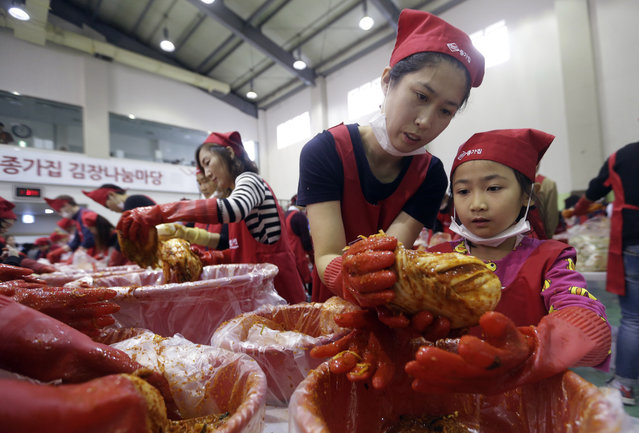 Roh Hae-kyung and her daughter Han Soo-a, right, make kimchi, traditional pungent vegetable, to donate to needy neighbors for winter preparation at a government building in Seoul, South Korea, Wednesday, October 28, 2015. About 100 volunteers made 5,500kg of kimchi. Made with cabbage, other vegetables and chili sauce, kimchi is the most popular traditional food in Korea. (Photo by Ahn Young-joon/AP Photo)