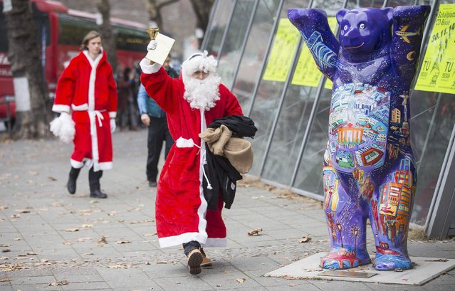 A man dressed as Santa Claus leaves the annual meeting of participants of a university rent-a-Santa Claus service in Berlin November 29, 2014. Some 100 people in Santa Claus and fairy costumes met on Saturday in Berlin for a general meeting to launch the annual Student Union charitable Santa Claus rental campaign. (Photo by Hannibal Hanschke/Reuters)
