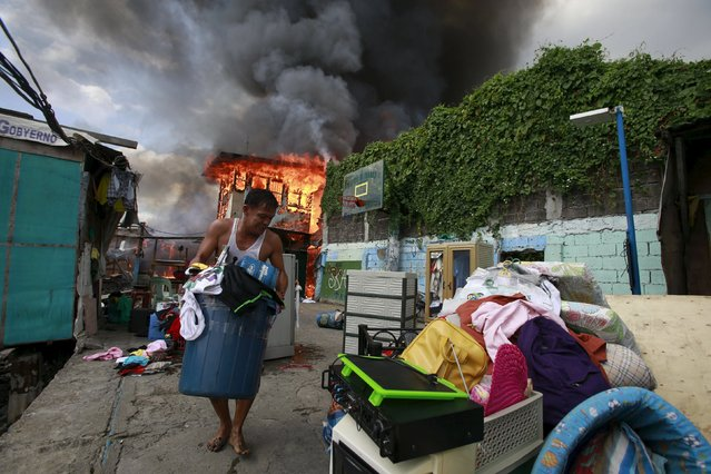 A resident saves their belongings while a fire razed residential area of Tambo town, Paranaque city, south of Manila October 29, 2015. At least some 50 houses made of light materials were destroyed by fire, affecting 150 families according to a Bureau of Fire Protection (BFP) official. (Photo by Romeo Ranoco/Reuters)