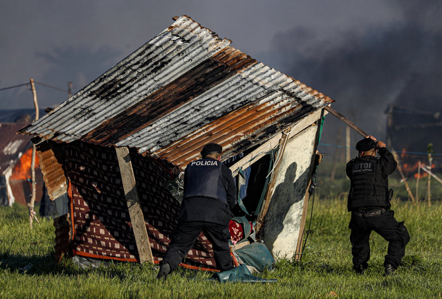 Police destroy a shack home as they carry out evictions at a squatters camp in Guernica, Buenos Aires province, Argentina, Thursday, October 29, 2020. (Photo by Natacha Pisarenko/AP Photo)