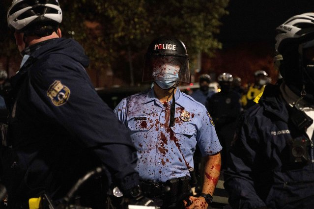A riot police officer stands with a red smoothie splashed on him during clashes at a rally after the death of Walter Wallace Jr., a Black man who was shot by police in Philadelphia, Pennsylvania, October 27, 2020. Wallace, 27, was gunned down on October 26 by two police officers responding to what his relatives say was a call for assistance with a mental health crisis. (Photo by Yuki Iwamura/Reuters)