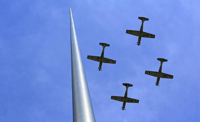 Aircraft from the Irish Defence Forces  fly past the Spire on O'Connell Street, Dublin, during the 97th anniversary of the 1916 Easter Rising against British rule in Ireland, on March 31, 2013. (Photo by Julien Behal/PA Wire)