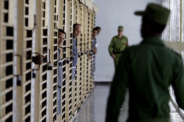 Prisoners look at military guards as they return to their cells at the Combinado del Este prison during a media tour in Havana, Cuba, Tuesday, April 9, 2013. Cuban authorities led foreign journalists through the maximum security prison, the largest in the Caribbean country that houses 3,000 prisoners. Cuba says they have 200 prisons across the country, including five that are maximum security. (Photo by Franklin Reyes/AP Photo)
