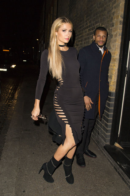 Paris Hilton and friends arriving at the Chiltern Firehouse in a black slit dress at midnight, October 6, 2016. (Photo by Splash News and Pictures)