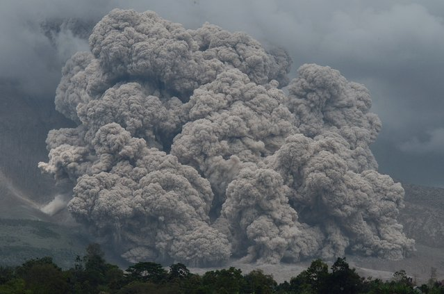 Thick and hot smoke spews from Mount Sinabung in Karo on December 9, 2014. Indonesian local government relocated residents who lives in danger zones around Mount Sinabung following deadly eruptions in early February 2014 that killed about 17 people. (Photo by Sutanta Aditya/AFP Photo)