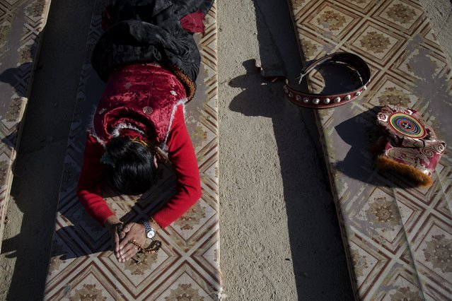 A traditional Tibetan hat and belt are put aside as an ethnic Tibetan woman prostrates herself at a monastery above the Larung Wuming Buddhist Institute, located some 3700 to 4000 metres above the sea level in remote Sertar county, Garze Tibetan Autonomous Prefecture, Sichuan province, China November 1, 2015. (Photo by Damir Sagolj/Reuters)