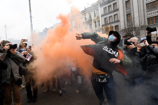 A demonstrator throws a smoke bomb during a protest action of representatives of different Ukrainian political parties and movements outside the constitutional court building in Kiev on October 30, 2020. Activists protested against the ruling of Ukraine's constitutional court that blocked a number of anti-corruption laws including on free public access to officials' declarations, a significant rollback of Ukraine's anti-corruption reforms. (Photo by Sergei Supinsky and Thomas Coex/AFP Photo)