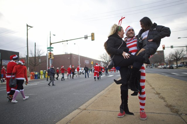 "Melissa Sherman (L), 28, and Anne White (R), 29, are lifted by Kurt Stine, 28, during the ""Running of the Santas"" in Philadelphia, Pennsylvania December 13, 2014. (Photo by Mark Makela/Reuters)"