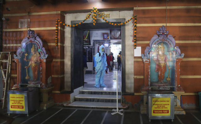 An employee sanitises a Hindu temple in Mumbai, India, Sunday, November 15, 2020. India is second in the world in total reported coronavirus cases behind the U.S., but daily infections have been on the decline since the middle of September. (Photo by Rafiq Maqbool/AP Photo)