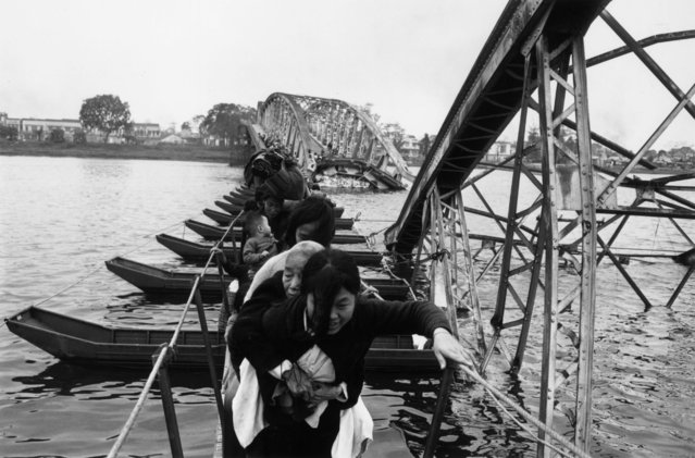 Vietnamese refugees crossing the Perfume River, 1968. The bridge has been destroyed during fighting, and the refugees must balance on a series of boats to cross to the other side. (Photo by Terry Fincher/Daily Express/Hulton Archive/Getty Images)