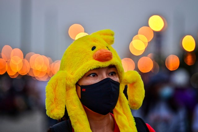 A pro-democracy protester wears a hat in the shape of a yellow rubber duck, which has become a recent symbol for the ongoing protests, during an anti-government rally in Bangkok on November 22, 2020. (Photo by Lillian Suwanrumpha/AFP Photo)