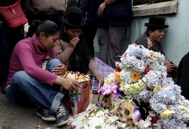 """Aymara women sit near skulls placed on the floor during a ceremony held for the """"Dia de las natitas"""" (Day of the Skull) celebrations at the General Cemetery of La Paz, November 8, 2015. Bolivians, who keep close relatives skulls at home as a macabre talisman, flock to the cemetery chapel once a year to have the craniums blessed and to bring themselves good luck in the future. (Photo by David Mercado/Reuters)"""
