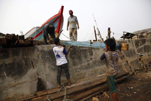 Men hoist lumber over the sea wall in Muara Baru, north Jakarta, October 7, 2014. Picture taken October 7, 2014. (Photo by Darren Whiteside/Reuters)
