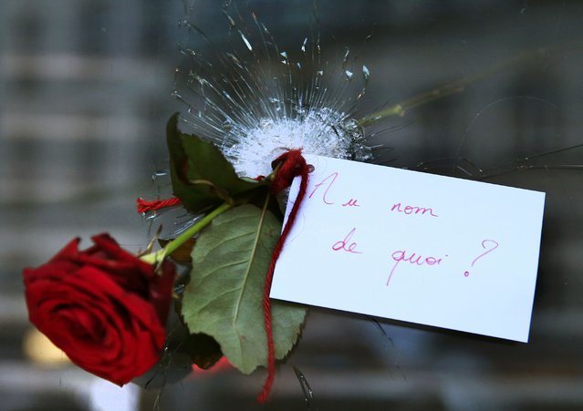 "A rose placed in a bullet hole in a restaurant window the day after a series of deadly attacks in Paris, November 14, 2015. The note reads ""In the Name of What?"". (Photo by Pascal Rossignol/Reuters)"