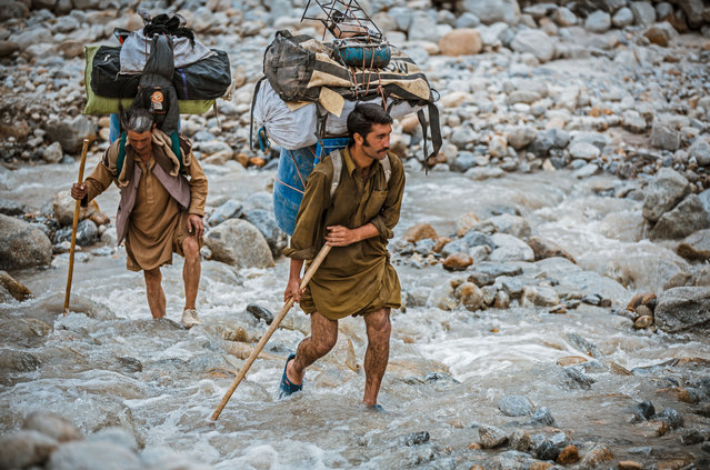 Balti porters carrying loads which range from 25kg to 50kg, a task they undertake often wearing only basic rubber sneakers filled with fresh grass to stop their feet slipping. (Photo by David Kaszlikowski/Rex Features)