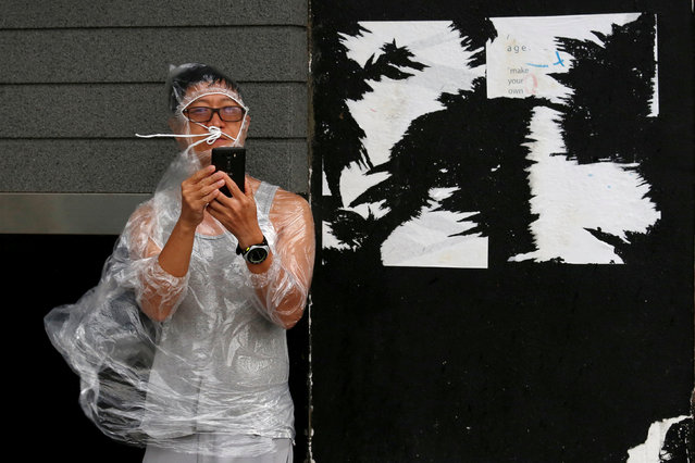 A man uses a smartphone under strong winds near a waterfront as Typhoon Haima approaches in Hong Kong, China, October 21, 2016. (Photo by Bobby Yip/Reuters)