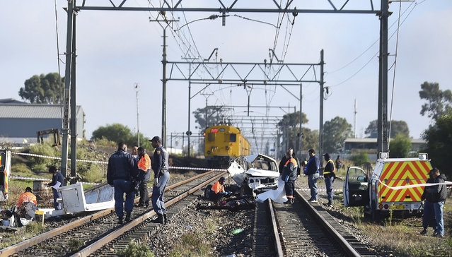 Emergency workers attend the scene where a train struck a vehicle at a railway crossing in Cape Town, South Africa, Friday April 27, 2018. A train in South Africa has struck a vehicle at a railway crossing, killing seven men in the same place where 10 children died in a similar accident in 2010. (Photo by AP Photo)