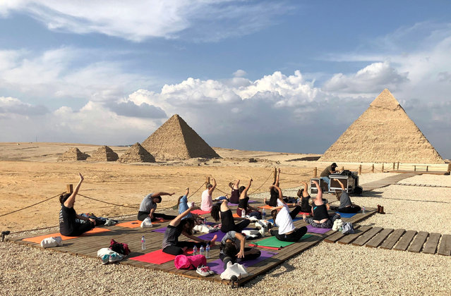 Women attend a Yes Yoga Day event in support of the eradication of violence against women amid the coronavirus disease (COVID-19) in front of the historical Giza pyramids, Egypt, November 7, 2020. (Photo by Ahmed Fahmy/Reuters)