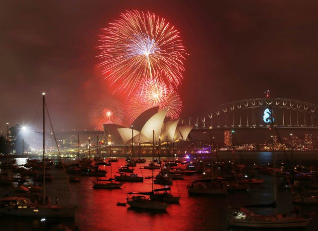 Fireworks light up the Sydney Opera House during an early light show before the midnight New Year fireworks, December 31, 2014. (Photo by Jason Reed/Reuters)