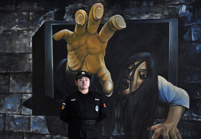 "A security guard stands in front of a 3D painting outside a ""haunted house"" in Hefei, Anhui province December 31, 2014. (Photo by Reuters/Stringer)"