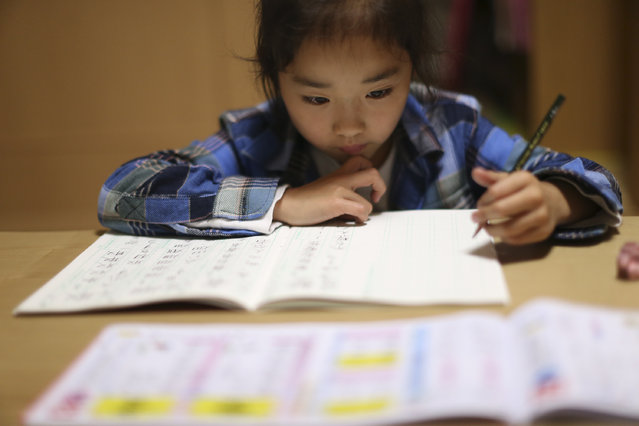In this November 18, 2015 photo, 9-year-old Mahiro Takano, three-time Japan karate champion in her age group, does her school homework's at home before going to her karate practice in Nagaoka, Niigata Prefecture, north of Tokyo. (Photo by Eugene Hoshiko/AP Photo)