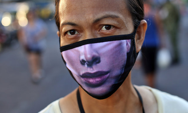 A Filipino woman wears a mask to try and protect against the spread of coronavirus in Malate district, Manila City on March 24, 2020. The Philippines has taken drastic measures to combat the spread of Covid-19. The entire country is under strict quarantine and the army is on the streets to monitor compliance. According to official figures, there are 462 positive cases and 33 dead in the Philippines, but it is thought that thousands of cases remain undetected due to lack of resources in a country where millions of people have no access to health care. In the poorest and most crowded areas, it's almost impossible to adhere to the physical distancing required during quarantine. (Photo by Alejandro Ernesto/The Guardian)