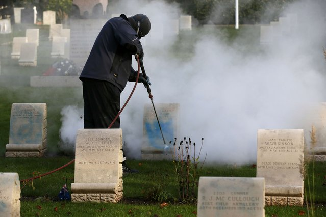 A worker cleans paint off a gravestone at the Harefield churchyard in Hillingdon, Britain November 23, 2015. Graves of Australian and New Zealand soldiers killed in World War One have been daubed with graffiti for the second time in seven months in London. Headstones of Australian and New Zealand Army Corps (ANZAC) graves were graffitied with blue paint at a churchyard in Hillingdon, west London. (Photo by Stefan Wermuth/Reuters)