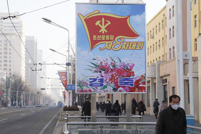 People walk past a billboard announcing the 8th Congress of the Workers' Party along a main street of the Central District in Pyongyang, North Korea, on Wednesday, January 6, 2021. (Photo by Jon Chol Jin/AP Photo)