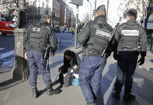 French Gendarmes check a passerby's bag as they secure the access to the solidarity march (Rassemblement Republicain) in the streets of Paris January 11, 2015. French citizens will be joined by dozens of foreign leaders, among them Arab and Muslim representatives, in a march on Sunday in an unprecedented tribute to this week's victims following the shootings by gunmen at the offices of the satirical weekly newspaper Charlie Hebdo, the killing of a police woman in Montrouge. (Photo by Eric Gaillard/Reuters)