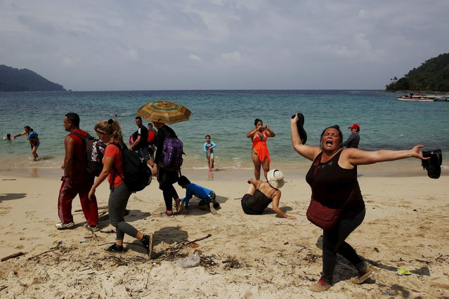 """A Cuban migrant shouts """"Cuba"""" after arriving to the beach after crossing the border from Colombia through the jungle as tourist stand by in La Miel, in the province of Guna Yala, Panama December 2, 2015. According to local authorities in La Miel, some 100 to 150 Cubans have been entering Panama from Colombia every day for the last three months. (Photo by Carlos Jasso/Reuters)"""