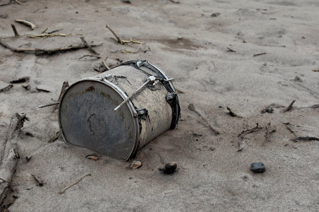 A drum covered with ash lies outside a house affected by the eruption of the Fuego volcano at San Miguel Los Lotes in Escuintla, Guatemala, June 6, 2018. (Photo by Carlos Jasso/Reuters)