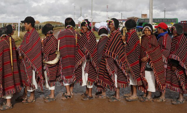 Supporters of Bolivia's Evo Morales line up to enter the sacred Kalasasaya temple to participate in a religious ritual in which Morales will be recognized as the country's leader by Aymaras spiritual guide at the archeological site Tiwanaku, Bolivia, Wednesday, January 21, 2015. (Photo by Juan Karita/AP Photo)