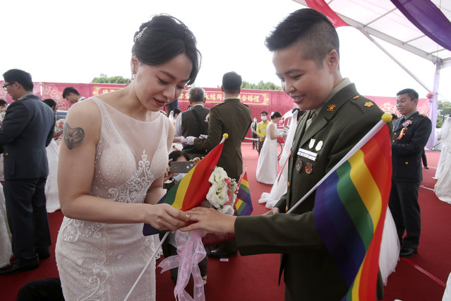 Lesbian couple Yumi Meng, left, puts a ring on Yi Wang' s finger during a military mass weddings ceremony in Taoyuan city, northern Taiwan, Friday, October 30, 2020. Two lesbian couples tied the knot in a mass ceremony held by Taiwan's military on Friday in a historic step for the island. Taiwan is the only place in Asia to have legalized gay marriage, passing legislation in this regard in May 2019. (Photo by Chiang Ying-ying/AP Photo)