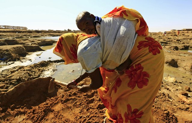 An internally displaced woman carries her child while digging the ground for mud to construct a house at the Aboushok camp in El Fasher, North Darfur, Sudan, November 17, 2015. (Photo by Mohamed Nureldin Abdallah/Reuters)
