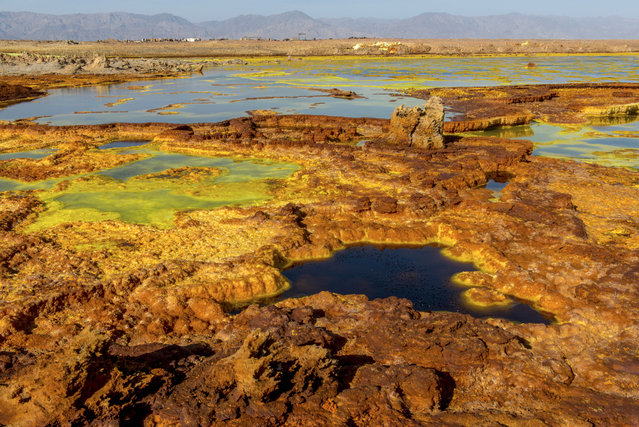 These stunning images show the beauty and drama of Mother Nature at work. Captured deep in heart of the Danakil Desert in East Africa, the images show the acid pools near the Erta Ale volcano. Pools of brightly colored acid can be seen amid the dramatic blast of volcanic ash. The photos were taken by Neta Dekel, an Israeli photographer. He the acid pools were one of the most extraordinary sights he had ever seen. (Photo by Neta Dekel/Caters News Agency)